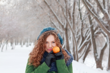 Beautiful girl holds mandarin and looks at camera at winter day in park photo