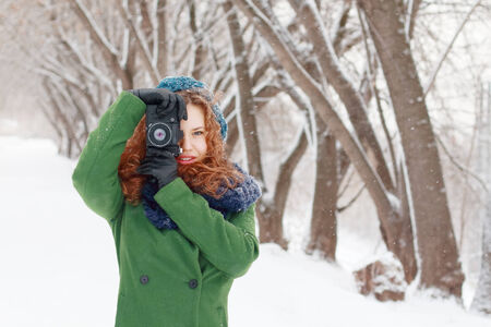 Beautiful girl holds photographs by retro camera at winter day in park photo