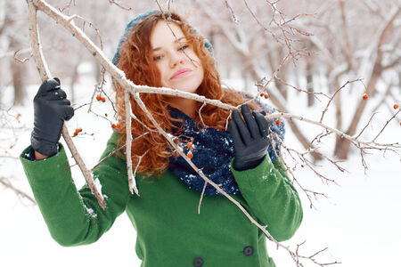 Girl clings to branch with berries at winter photo