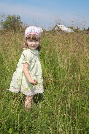 Pretty little girl in dress stands among high grass at meadow at summer sunny day photo