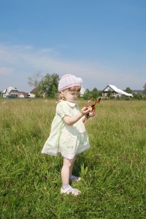 Cute little girl looks at windmill at green meadow near village at summer sunny day photo