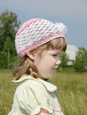 Smiling little girl looks away at meadow near village at summer sunny day photo
