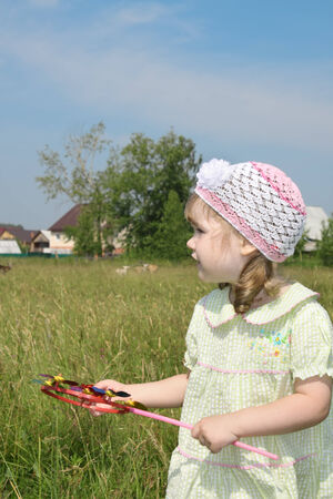 Little girl with windmill looks away at meadow near village at summer sunny day photo