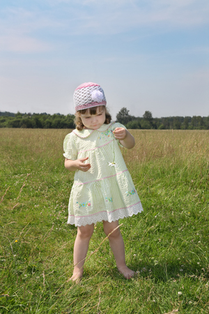 Little barefoot girl plays with camomile at green meadow at summer sunny day photo
