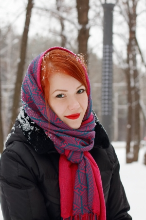 Beautiful girl in red kerchief smiles outdoor at winter day in park photo