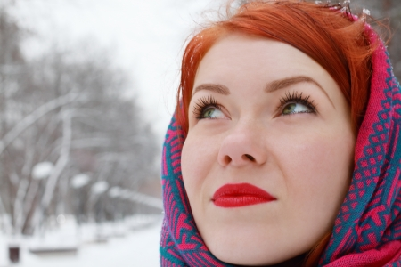 Pretty happy girl in red kerchief looks up outdoor at winter day in park photo