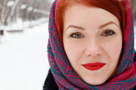 Pretty redhead girl in red kerchief looks outdoor at winter day in park photo