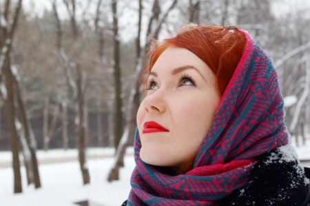 Pretty redhead girl in red kerchief looks up outdoor at winter day in park photo