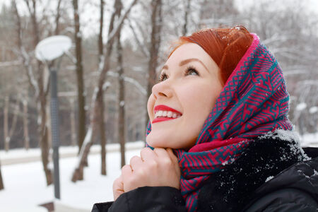 Pretty girl in red kerchief with clasped hands looks up outdoor at winter day in park photo