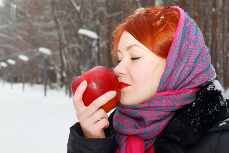 Pretty girl in red kerchief holds big red apple outdoor at winter day in park photo