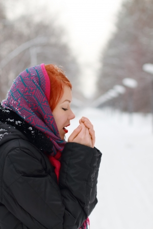 warms: Beautiful girl in shawl warms hands outdoor at winter day in park Stock Photo