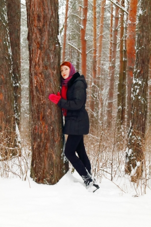 Beautiful girl stands next to large tree and looks up outdoor at winter day in forest photo