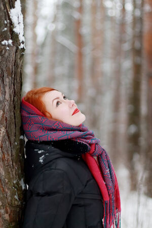 Smiling girl stands next to tree and looks up outdoor at winter day in forest photo