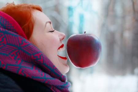 Smiling girl and hanging in air big red apple outdoor at winter day in forest photo