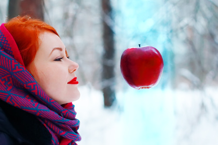Smiling girl looks at hanging in air big red apple outdoor at winter day in forest photo