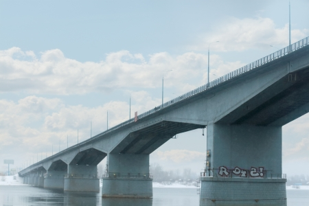 Grey bridge with lanterns over big river in snowy winter day photo
