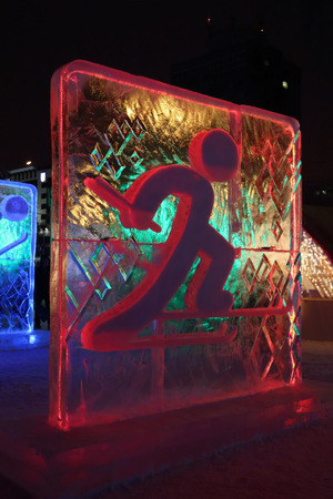 PERM, RUSSIA - JAN 11, 2014: Illuminated red Skier character sculpture in Ice town at evening, created in honor of Winter Olympic Games 2014 will be in Sochi, Russia.