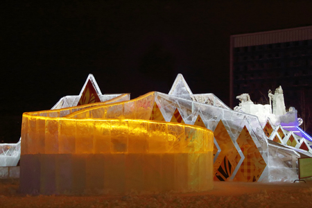 PERM, RUSSIA - JAN 11, 2014: Illuminated orange ice slide in Ice town at evening. Construction of Ice town of Perm was spent 590 thousand dollars.