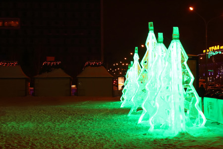 PERM, RUSSIA - JAN 11, 2014: Illuminated green ice Christmas trees in Ice town at evening. Construction of Ice town of Perm was spent 590 thousand dollars.