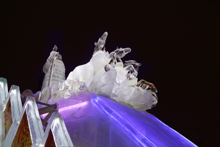 PERM, RUSSIA - JAN 11, 2014: Horse triple and Santa sculpture in Ice town at evening. Construction of Ice town of Perm was spent 590 thousand dollars.