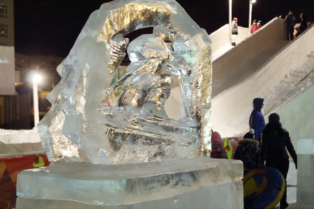 PERM, RUSSIA - JAN 11, 2014: Skier sculpture in Ice town at evening, created in honor of Winter Olympic Games 2014 will be in Sochi, Russia.