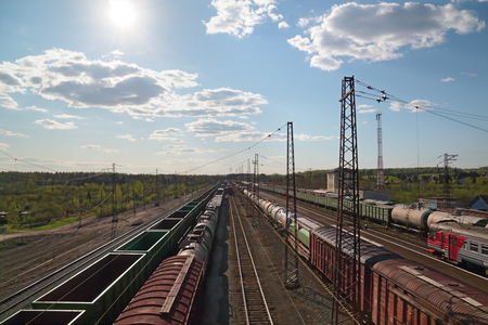 Sun and freight trains at railway station with old railroads at summer day photo
