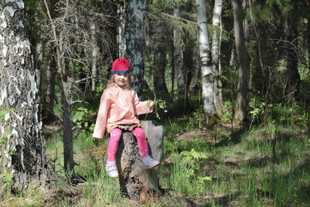 Happy pretty little girl in pink sits on tree stump in great forest at spring day photo