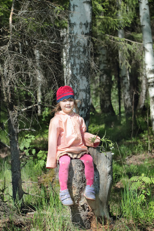 Beautiful little girl in pink sits on tree stump in dark forest at spring day photo