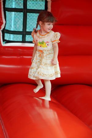 brincolin: Hermosa ni�a feliz salta sobre hinchable roja y se r�e Foto de archivo