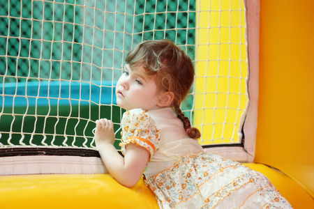 Little beautiful girl in dress stands in yellow bouncy and looks through net photo