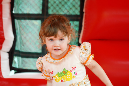 Little pretty happy girl in dress plays in red bouncy photo