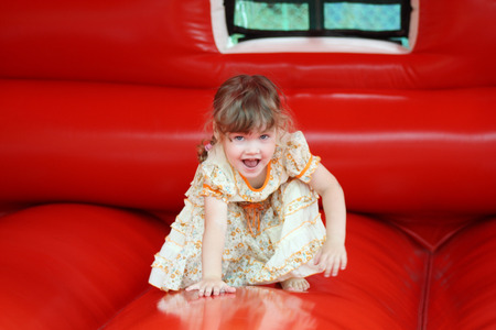 Little beautiful girl in dress plays in red bouncy photo