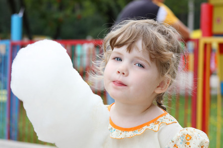 Little beautiful girl eating candy cotton at park in summer day photo