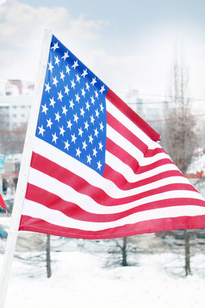 Flag of United States on wind at winter cloudy day in street of city
