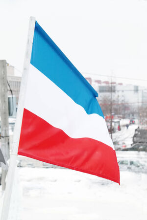 Flag of Netherlands at winter snowy and cloudy day in street of city Stock Photo