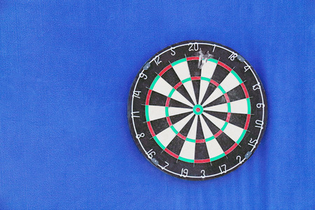 Round dartboard with numbers and with javelins on blue wall  photo