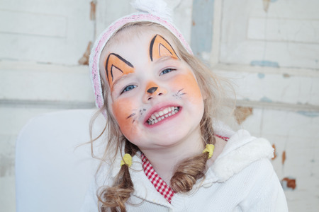 unnatural: Little beautiful girl with face painting of fox unnatural smiles