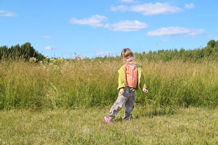 Little beautiful girl poses near tall grass at green meadow in sunny day photo