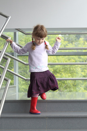 Little girl with two pigtails holding railing down stairs