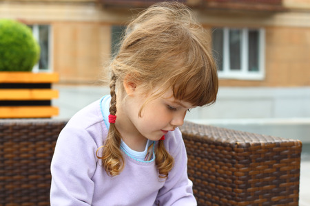 bowing head: Little girl with two braids sits on wicker couch bowing her head Stock Photo