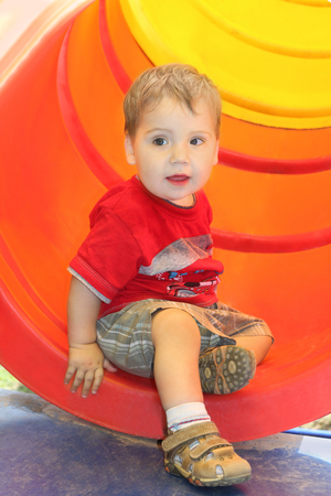 Portrait of little boy in red T-shirt near plastic tube on playground photo