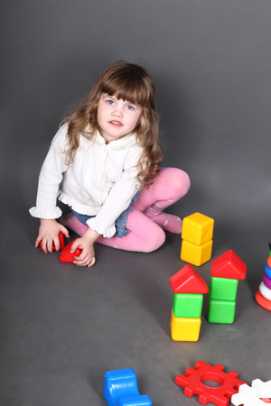builds: Little girl sitting on floor and builds tower of blocks