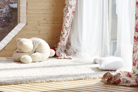 Sunlight from windows with white curtains, fluffy carpet and soft toy on wooden floor