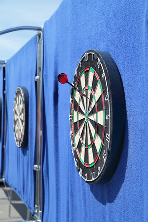 Dartboard with one javelin on blue wall on street in summer day photo