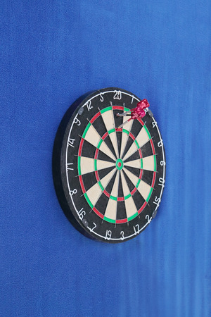 Dartboard with numbers and with three javelins on blue wall  photo