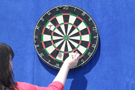 Woman removes darts from dartboard on blue wall at sunny day photo