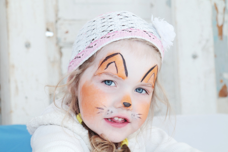 Little beautiful girl with face painting of orange fox poses in hat photo
