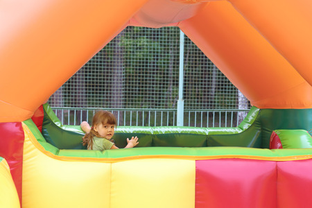 brincolin: Ni�a juega en el trampol�n de aire de color en el parque de atracciones Foto de archivo