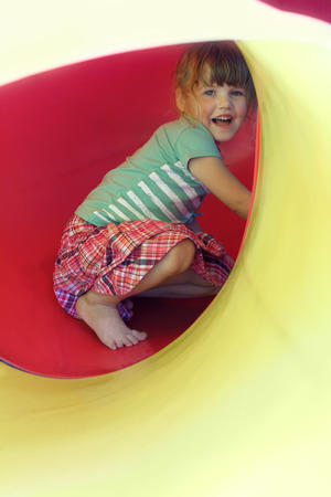 Portrait of happy little girl inside yellow plastic tube on playground photo