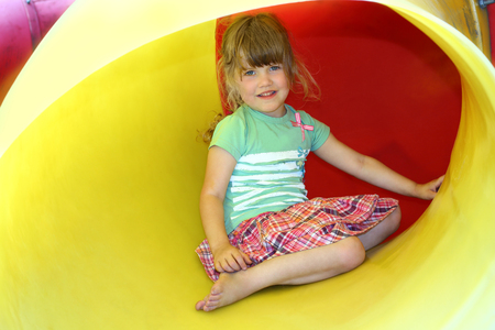 Portrait of smiling little girl inside yellow plastic tube on playground photo